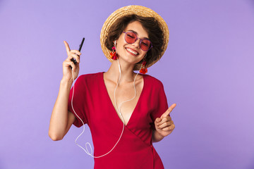 Wall Mural - Image of adorable brunette woman 20s in straw hat and earphones listening to music on cell phone, isolated over violet background