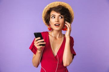 Image of young brunette woman 20s in straw hat and earphones listening to music on smartphone, isolated over violet background