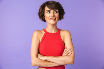 Image closeup of pretty brunette woman 20s in casual wear smiling while standing with arms crossed, isolated over violet background