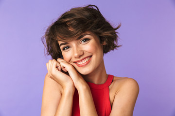 Wall Mural - Image closeup of caucasian satisfied girl 20s in casual wear smiling and holding hands at face, isolated over violet background