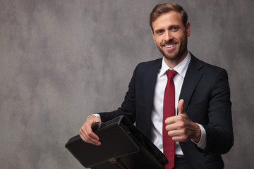 seated businessman holding briefcase makes ok sign