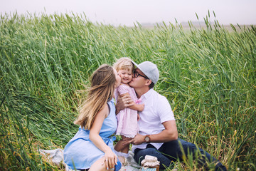 Family mother, father and little daughter beautiful and happy outdoors in the picnic field