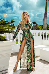 Beautiful, sexy blonde woman in an elegant evening gown posing on the background of the caribbean view