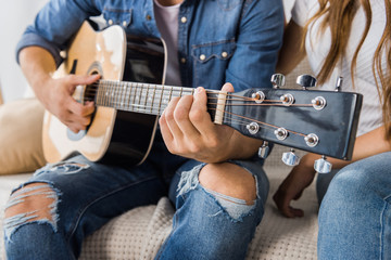 partial view of man playing on acoustic guitar while his girlfriend sitting near on couch at home