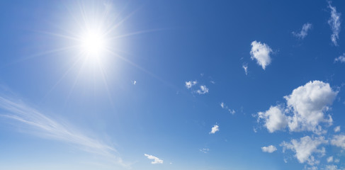 Background with sun and clouds on blue sky at summer