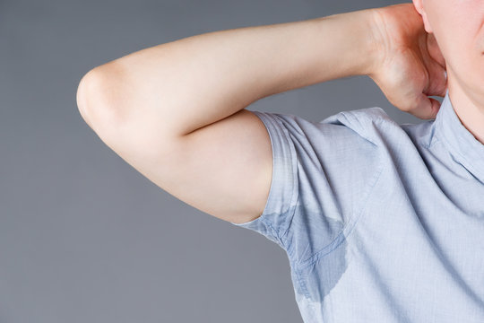 Man with sweaty armpits on gray background