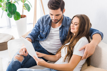young couple sitting on couch with digital tablet at home