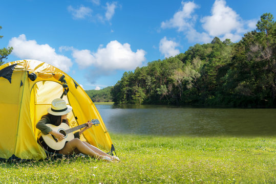 Happy traveler women on vacation camping with tents playing guitar in the forest near river.  Travel Concept