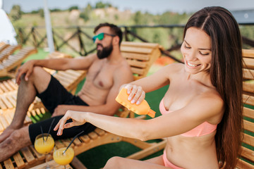 Nice and positive girl sits and puts some sunproof cream on skin. She holds orange bottle in right hand. Guy is serious. He sits and looks straight forward.