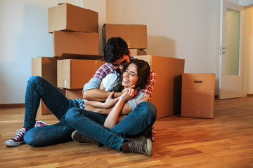 Young couple moving into a new home.They sitting on floor in empty apartment .Real estate concept.Embrace each other.
