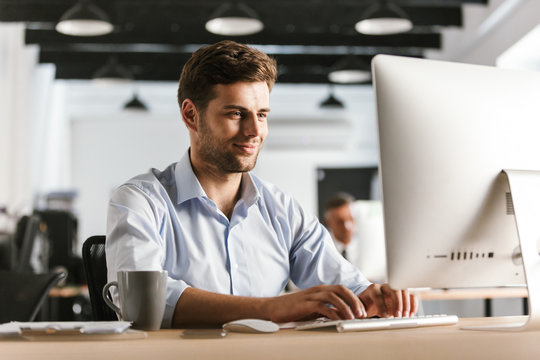 Image of Smiling business man using computer