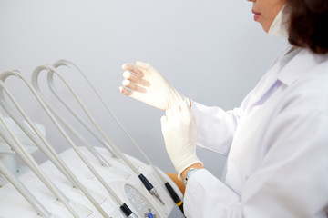Crop side view of woman in white gown putting on gloves before working with client in dental office