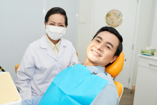 Asian man sitting in dental chair in office with smiling professional doctor in gown and mask near looking at camera