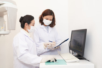 Side view of Asian women in white gowns exploring panoramic dental x-ray on computer screen and talking