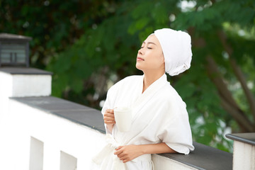 Beautiful Asian woman in white bathrobe and towel after shower standing with cup of coffee on terrace enjoying morning