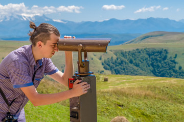 A young man in a blue shirt watches the mountains in a viewing binocular.