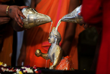 Hindu devotees pour milk over the idol of Hindu Lord Krishna during the festival of Janmashtami, marking the birth anniversary of Lord Krishna, in Ahmedabad