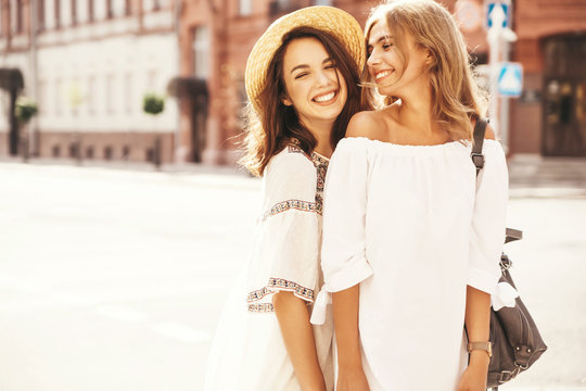 Fashion portrait of two young stylish hippie brunette and blond women models in summer sunny day in white hipster clothes posing on the street background. No makeup