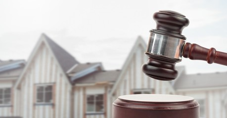 Gavel and houses on building construction site auction