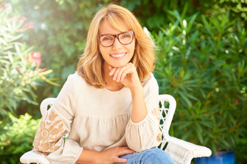 Mature beauty portrait. Happy middle aged woman wearing casual clothes and looking at camera while sitting in the garden and relaxing.