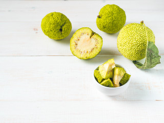 Green fruit of maclura pomifera,osage orange,horse apple,adam apple grow on white wooden table. Maclura pieces in plate ready for ointment preparation. Maclura use in alternative medicine. Copy space