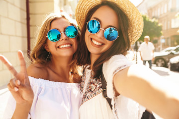 Two young female stylish hippie brunette and blond women models in hipster clothes taking selfie photos for social media on smartphone on the street background