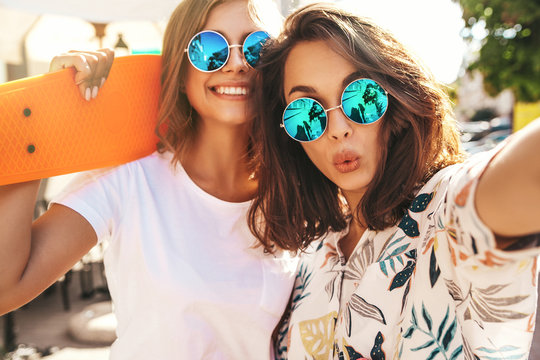 Two young female stylish hippie brunette and blond women models in summer hipster clothes taking selfie photos for social media on smartphone on the street background. With colorful penny skateboards