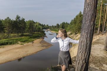 Девочка звонит по мобильному телефону стоя на высоком берегу реки.