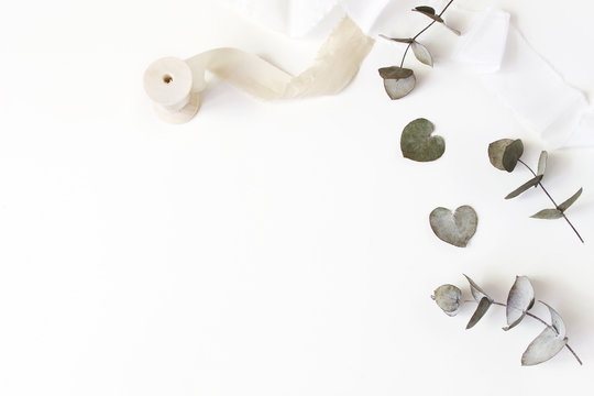 Feminine wedding desktop scene. Composition of dry silver dollar eucalyptus leaves and silk ribbons on white table background. Flat lay, top view.