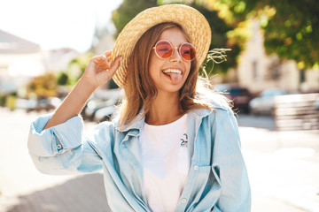 Portrait of beautiful cute smiling blond teenager model in summer hipster clothes posing on the street background. Showing her tongue.
