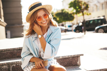 Portrait of beautiful cute blond teenager model in summer hipster clothes sitting on the street...