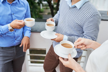 Faceless shot of casual coworkers standing with cups of coffee on terrace enjoying break time