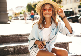 Portrait of beautiful cute smiling blond teenager model in summer hipster clothes sitting on stairs on the street background and listening music on her mobile phone