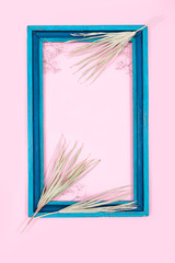 dry branches pink yellow leaves top view card copy space autumn blue frame background Valentine