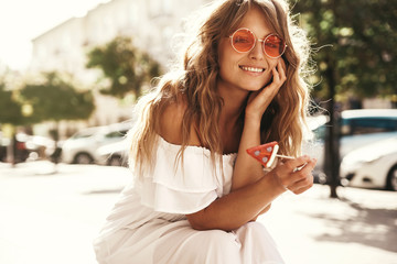 Portrait of beautiful cute blond teenager model with no makeup in summer hipster white dress clothes with watermelon candy sitting on the street background