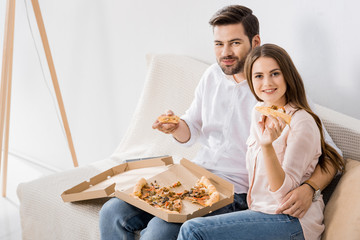 portrait of smiling young couple eating pizza at home