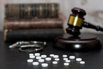 Judge's gavel with handcuffs, drugs on wooden table