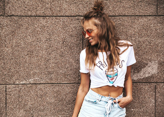 Beautiful cute blond teenager model  in summer hipster white clothes posing near wall on the street