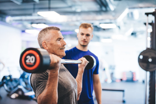 Older man lifting weights, supervised by gym assistant.