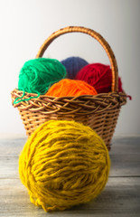 colored threads with a line of meters and a basket. on a light background and a wooden one