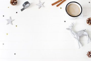 Christmas composition. Hot chocolate, pine cones, cinnamon sticks, stars confetti and reindeer on white table background. Creative winter holiday concept. Flat lay, top view