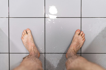 Male feet in shower. Concept of problem with potency. Man's health.