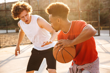 Portrait of american and caucasian men playing basketball at the playground outdoor, during summer sunny day