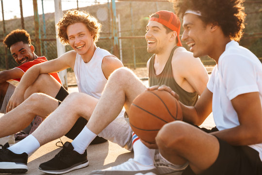 Young happy basketball players sitting at playground outdoor, and watching game during summer sunny day