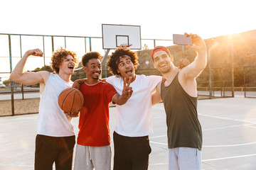 Strong multiethnic men smiling and taking selfie on smartphone, while playing basketball at playground outdoor during summer sunny day