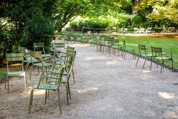 Green typical metal lawn chairs scattered alongside an alley of the Luxembourg garden in Paris, France, by a sunny summer morning.