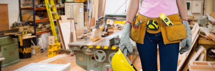 Composite image of woman with tool belt and holding hard hat