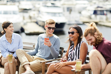 Happy young laughing people with drinks enjoying summer weekend by waterside