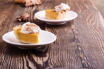 Slices of pumpkin pie with whipped cream on top, close-up