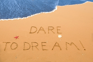 dare to dream written in the sand on a sunny beach